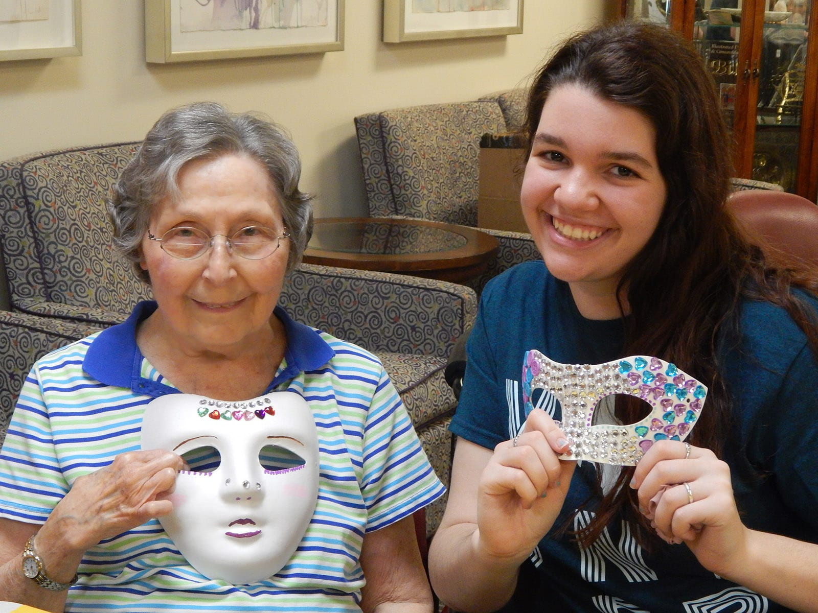 Medallion resident with student helper making Purim masks