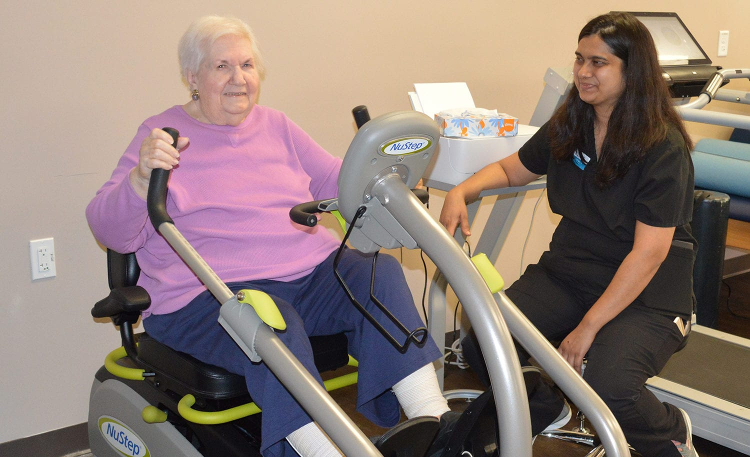 Skilled care resident on the ellyptical with therapist