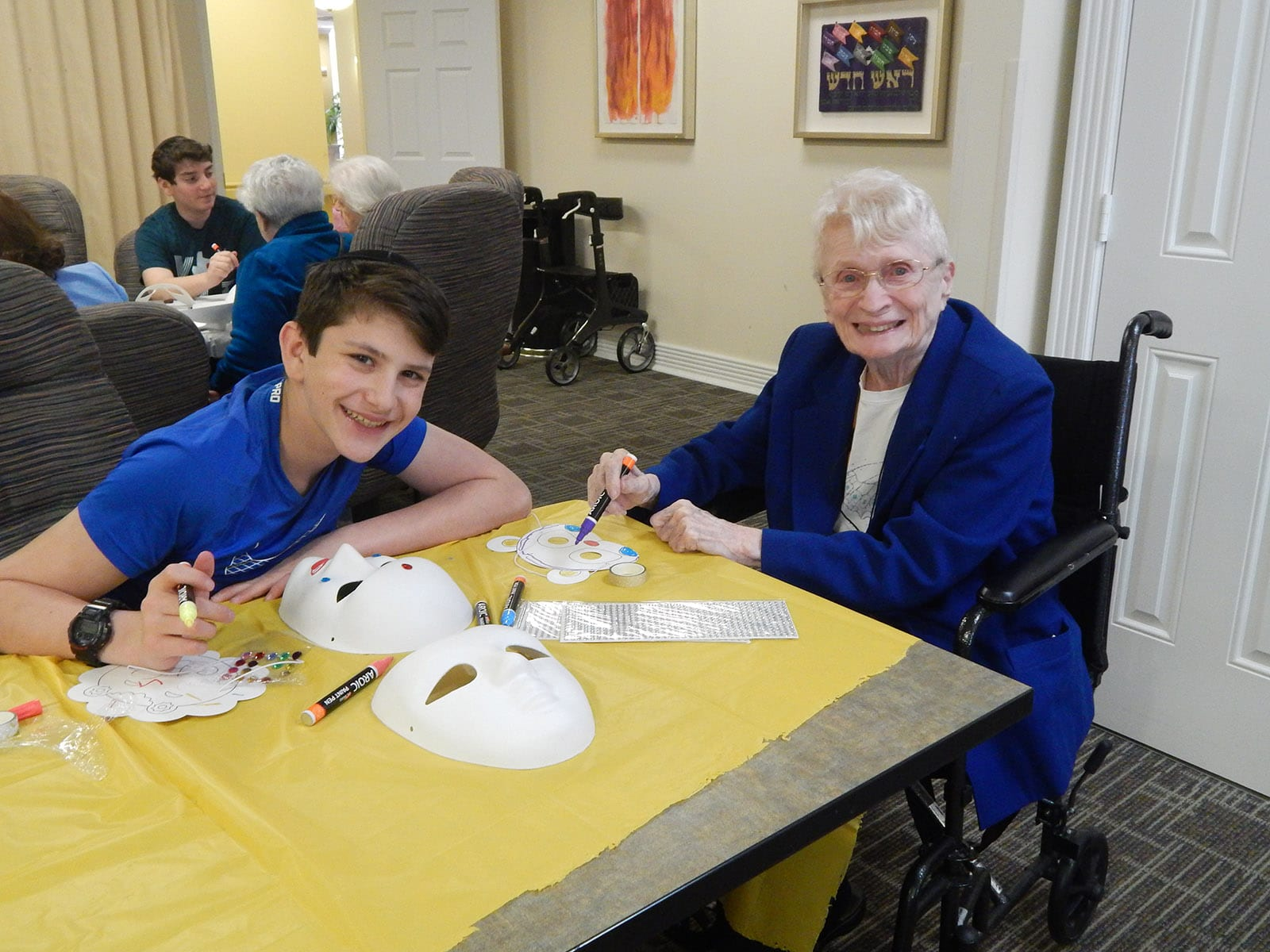 Student helping Medallion resident make a mask for Purim