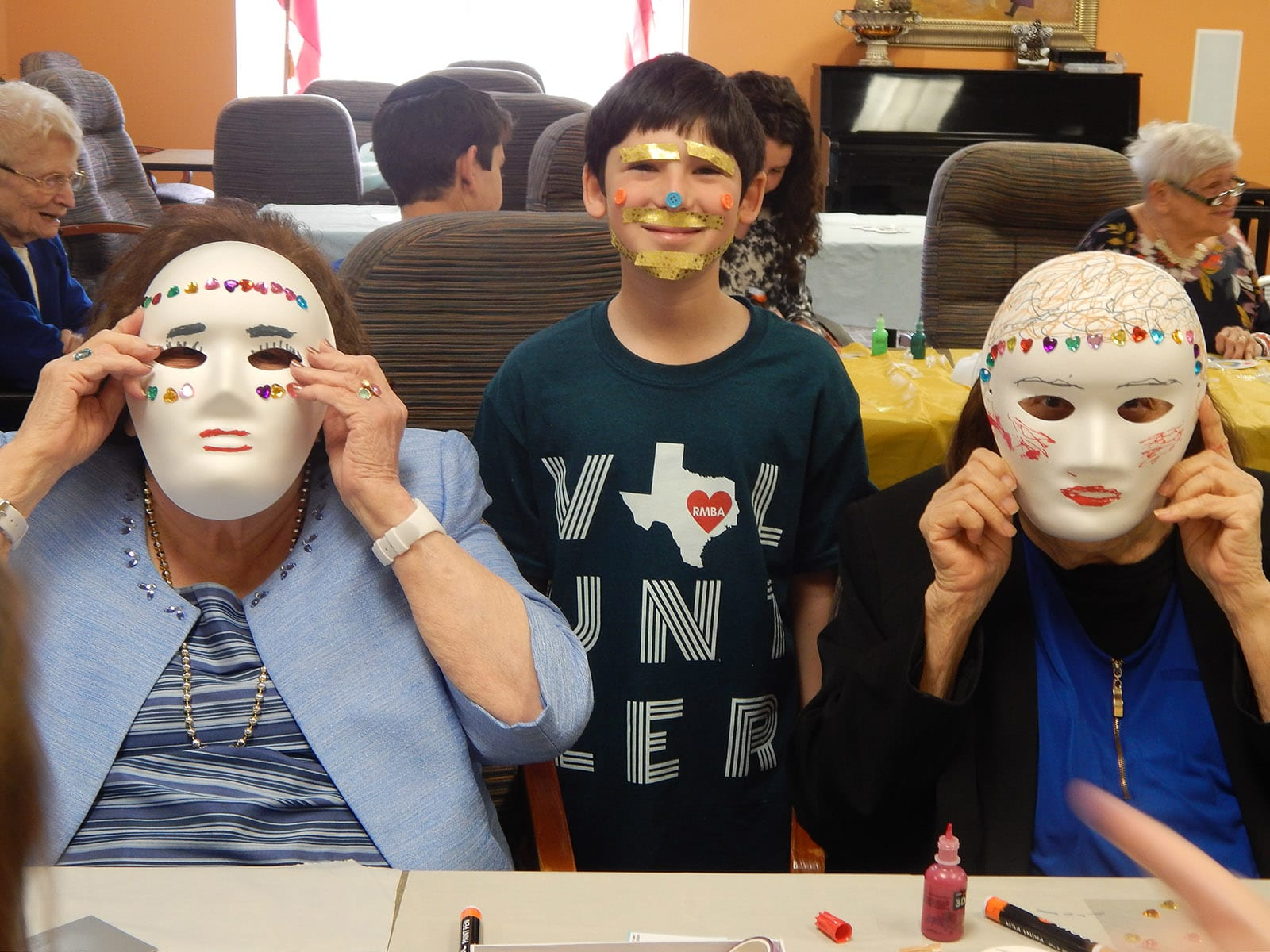 The Medallion residents are assisted by student in making masks for Purim